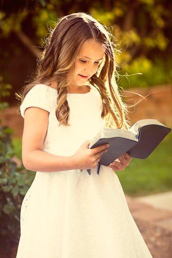 فتاة سعيدة تقرأ الكتاب المقدس
